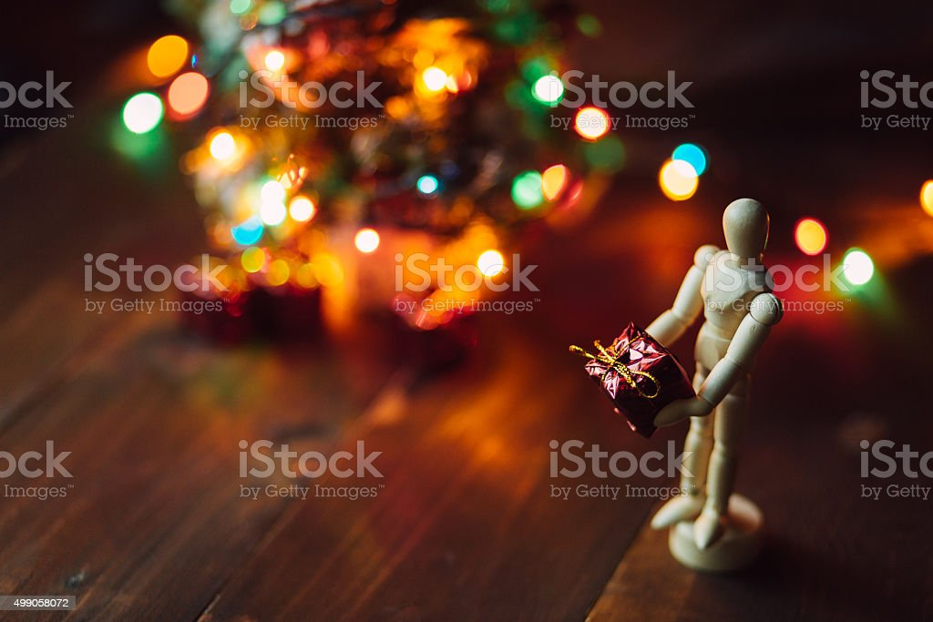Wooden hinged Mannequin with the gift and the Chritsmas tree stock photo