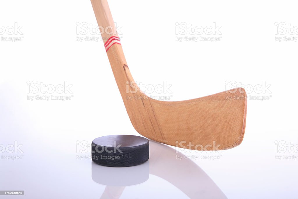 Wooden hockey stick & puck reflected on white background  stock photo