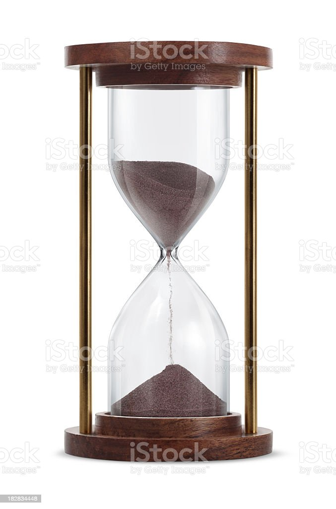 Wooden hourglass with brown sand running through it stock photo