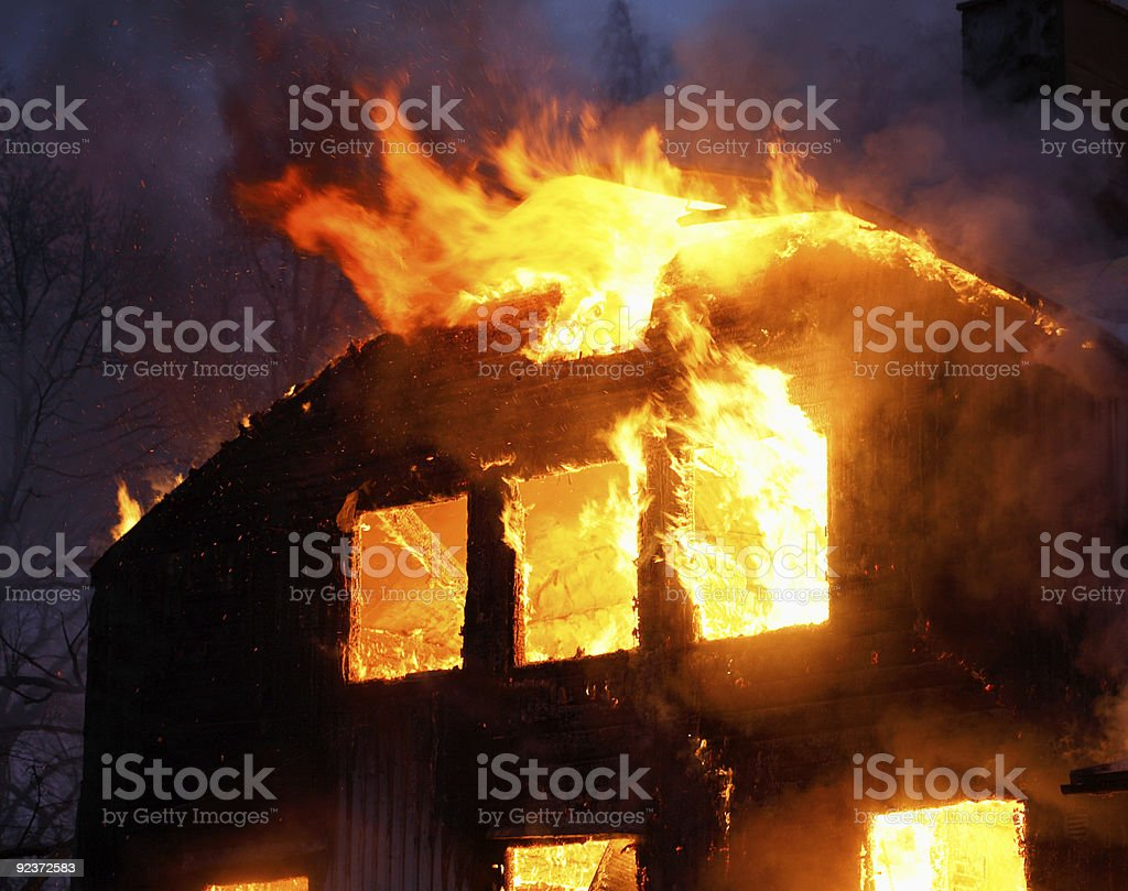 A wooden house in flames in the dark of night stock photo