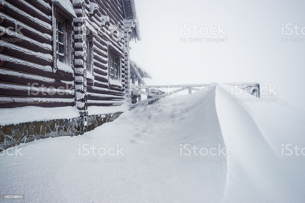 wooden house in snowdrift stock photo