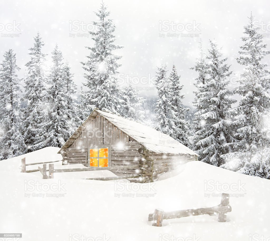 Wooden house in snowy mountains stock photo