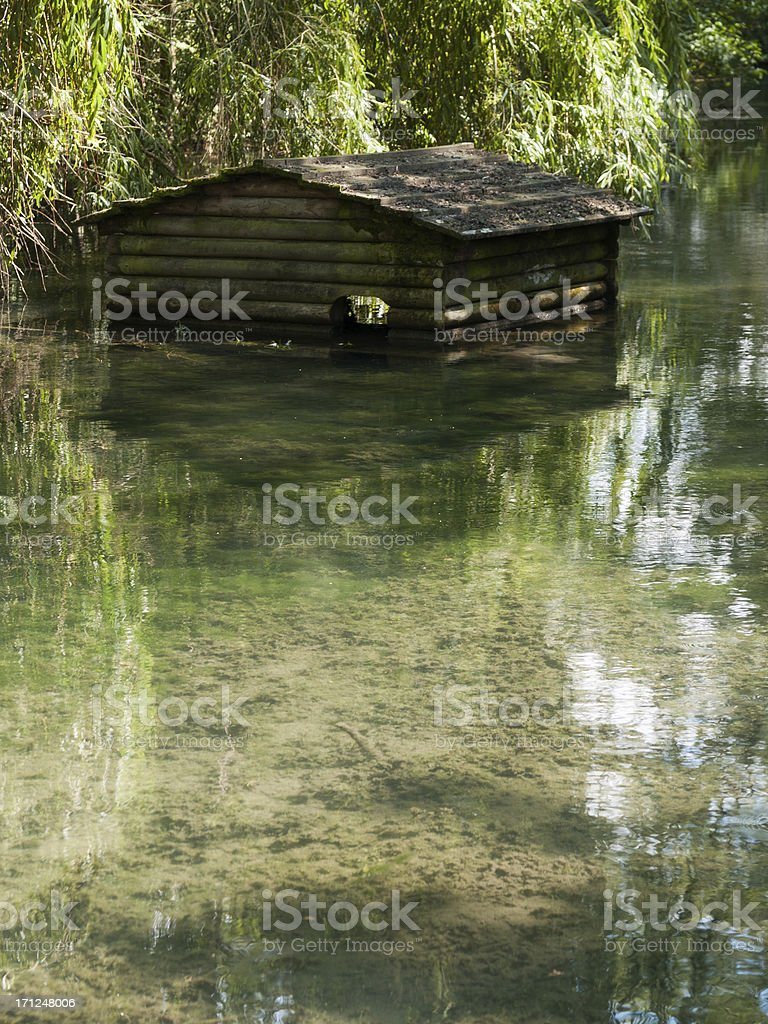 Wooden house stands in a quiet creek stock photo