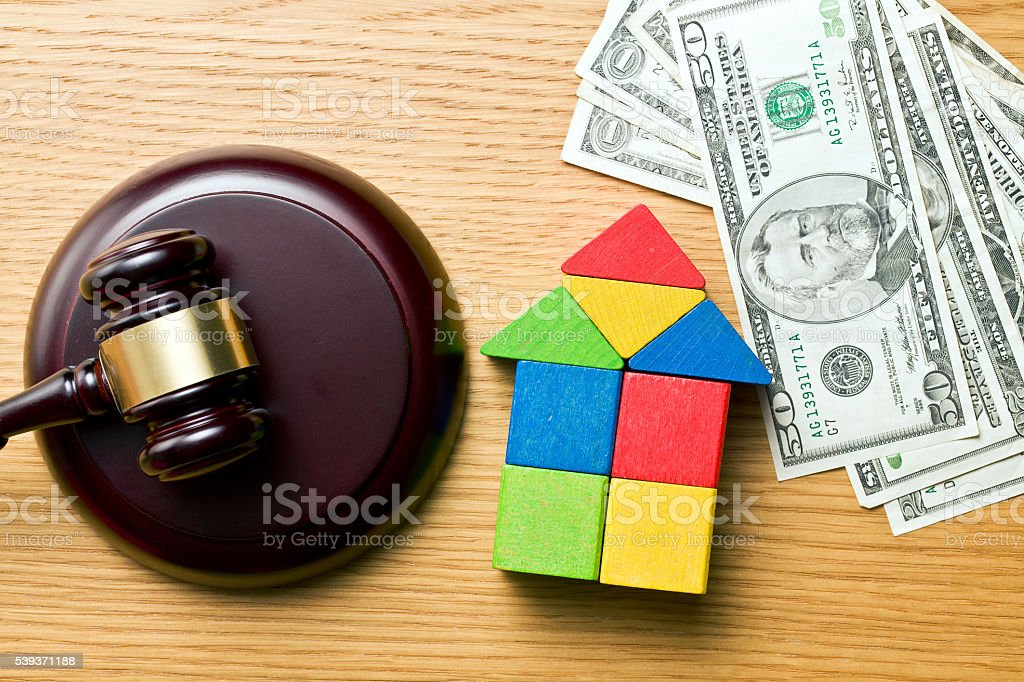 wooden house with money and judge gavel stock photo