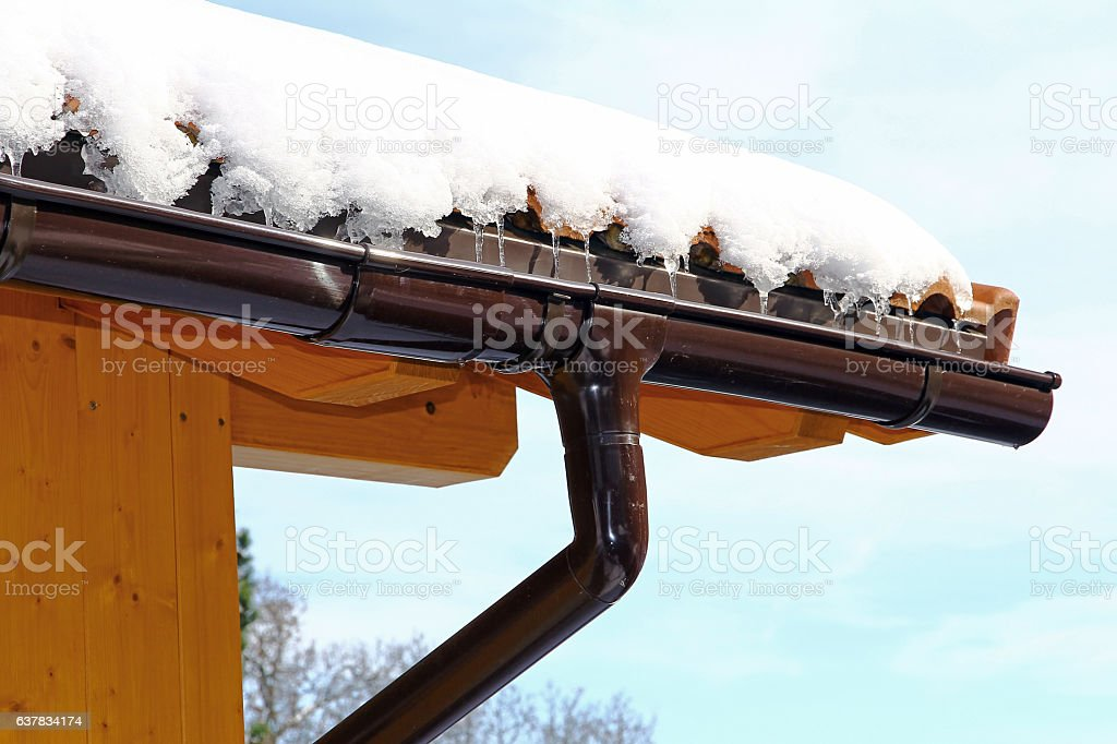 Wooden house with rain gutter in winter stock photo