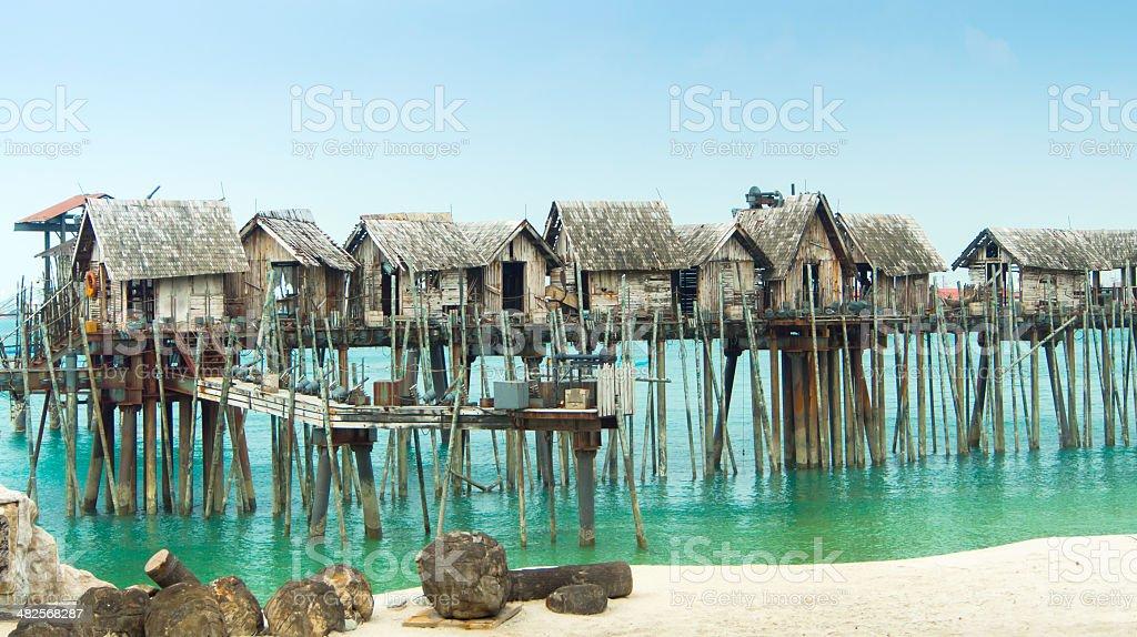wooden houses built across the shoreline stock photo