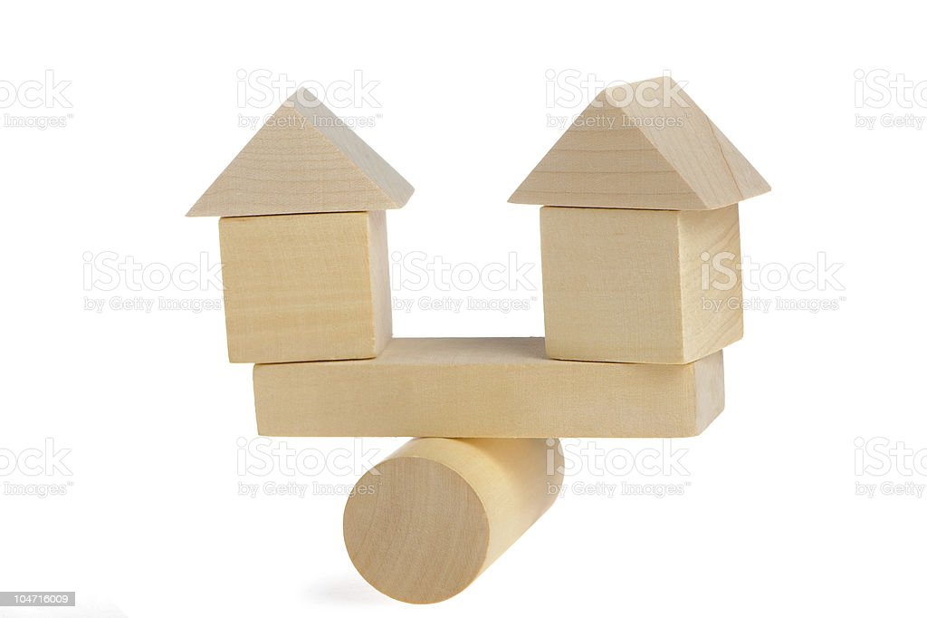 Wooden houses on abstract scales stock photo