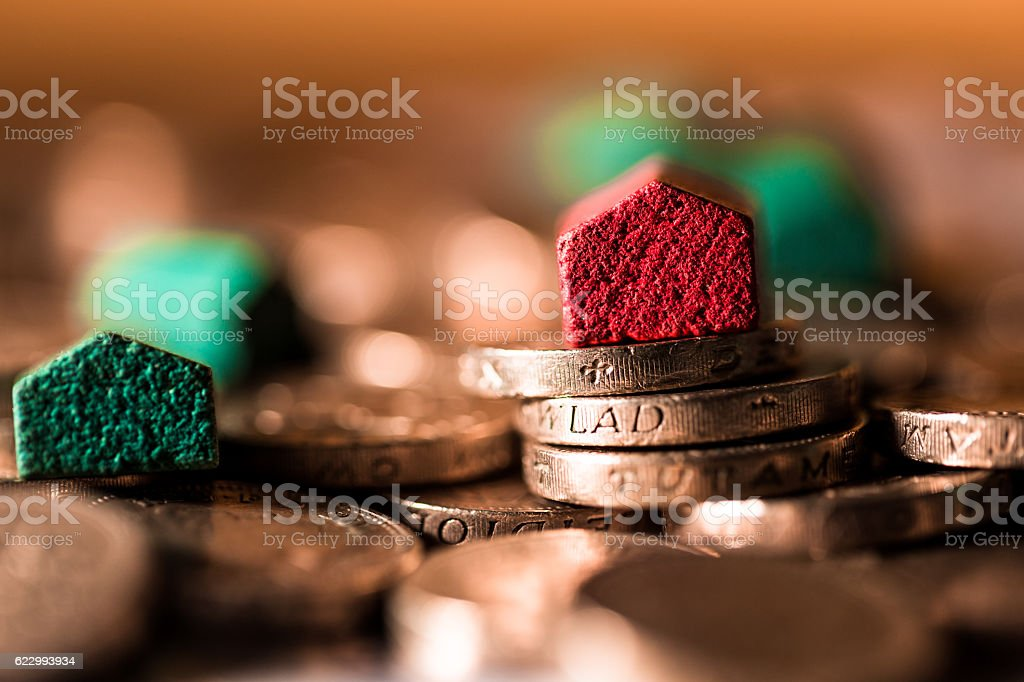 Wooden houses on top of pile of British pound coins stock photo