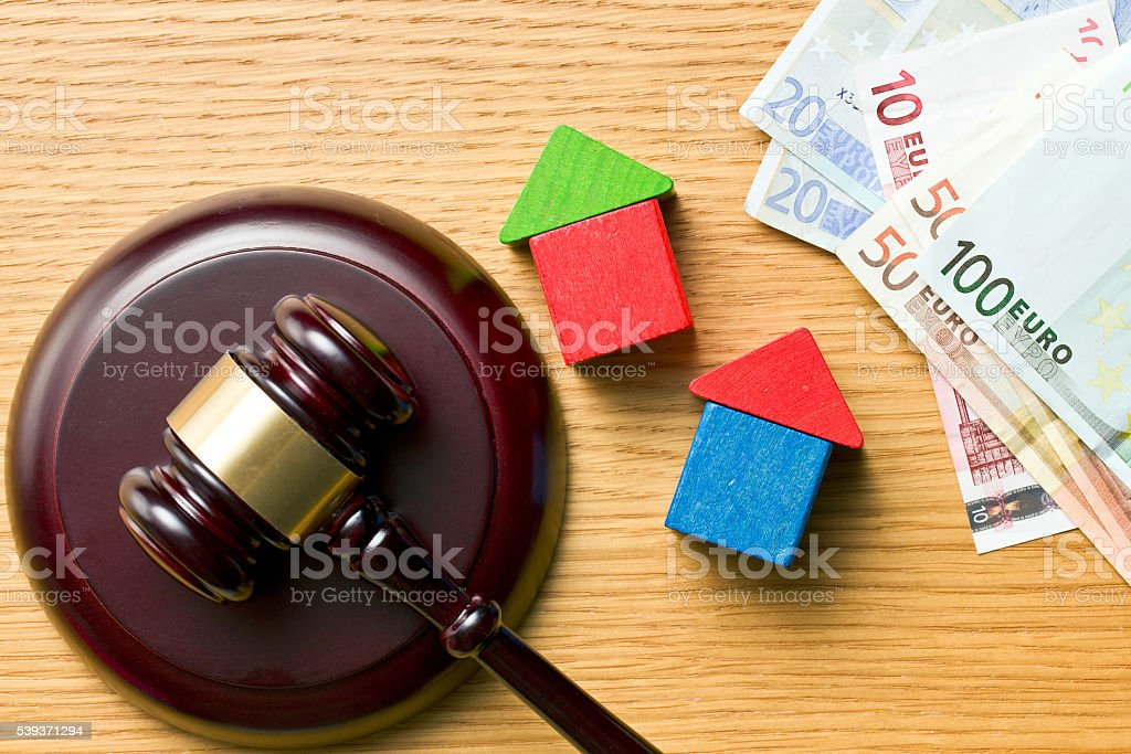 wooden houses with money and judge gavel stock photo