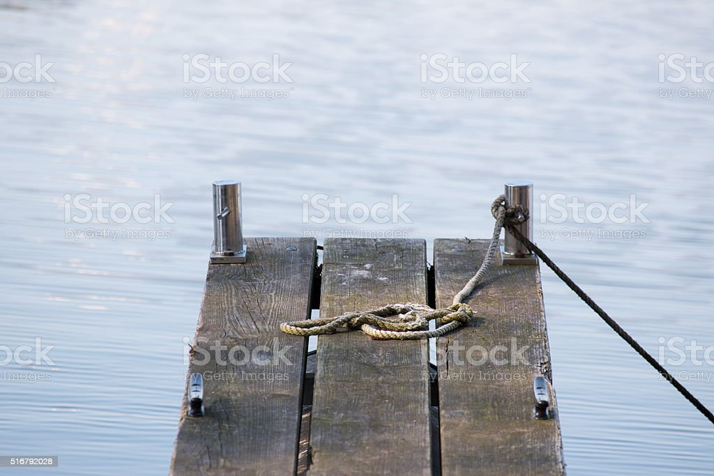 wooden jetty and an old rope in the blue water stock photo