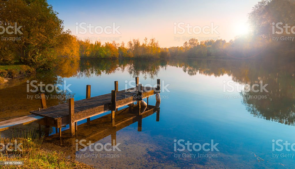 Wooden Jetty on a Becalmed Lake at Sunset stock photo