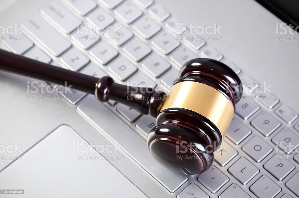 Wooden judge hammer on laptop computer white keyboard stock photo