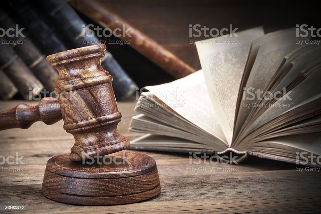 Wooden Judges Gavel And Old Law Books On Wooden Background stock photo