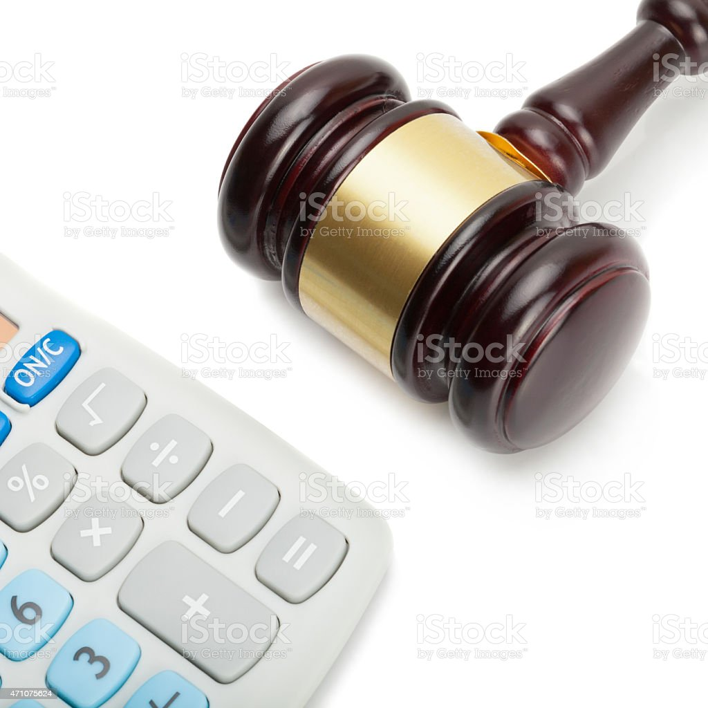 Wooden judge's gavel next to neat calculator - close up stock photo