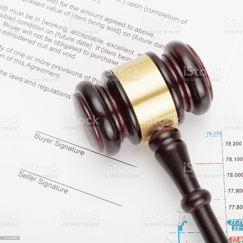 Wooden judge's gavel over unsigned contract - close up shot stock photo