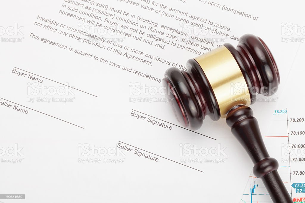 Wooden judge's gavel over unsigned contract stock photo