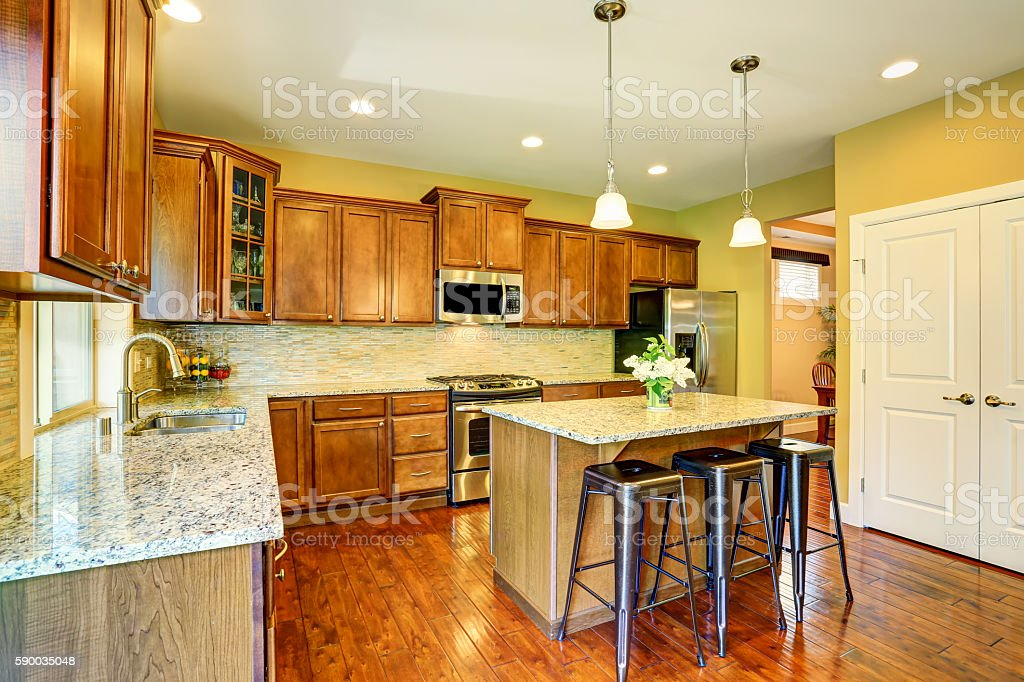 Wooden kitchen interior with kitchen island and cabinets. stock photo