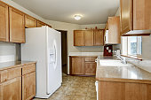 Wooden kitchen storage combination and white fridge