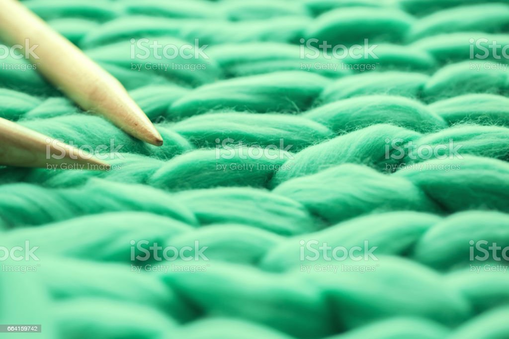 wooden knitting needles on background of merino wool stock photo