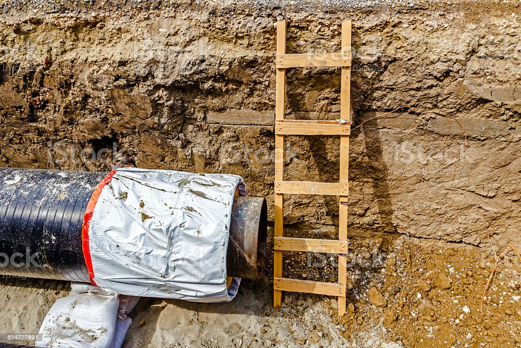 Wooden ladder in a fresh trench, layers of soil stock photo