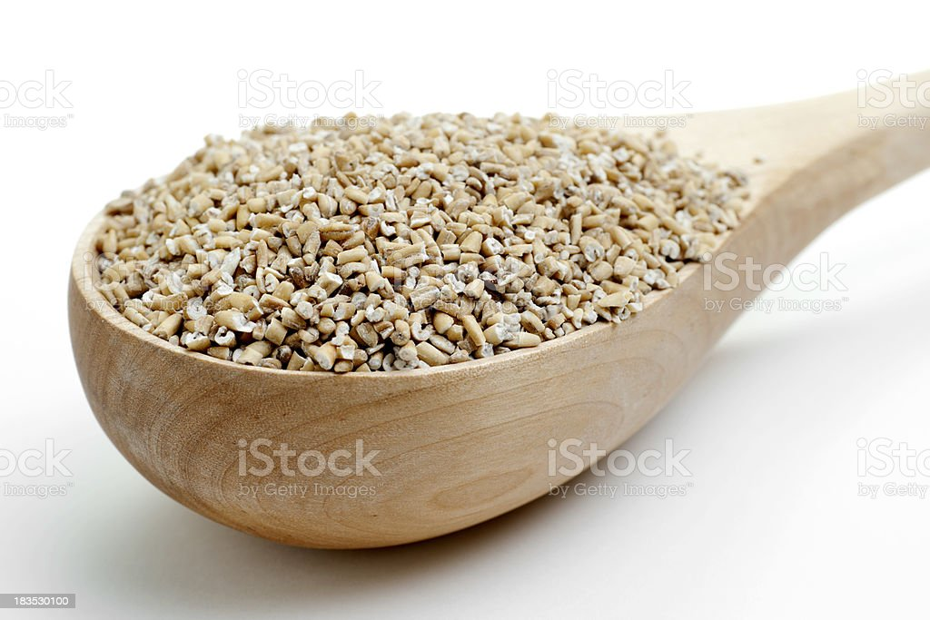 wooden ladle filled with steel cut oats stock photo