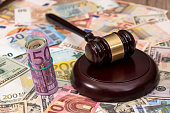 Wooden Law Gavel on Euro and Dollar background.