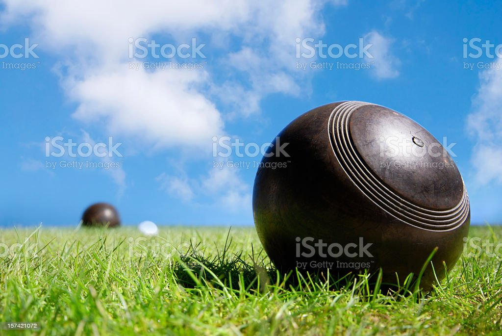 Wooden lawn bowls green grass under blue sky stock photo