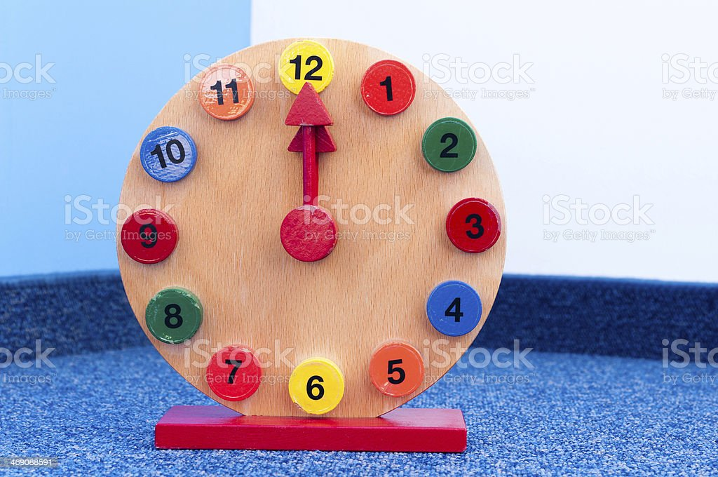 Wooden Learning Clock at twelve, noon, midnight stock photo
