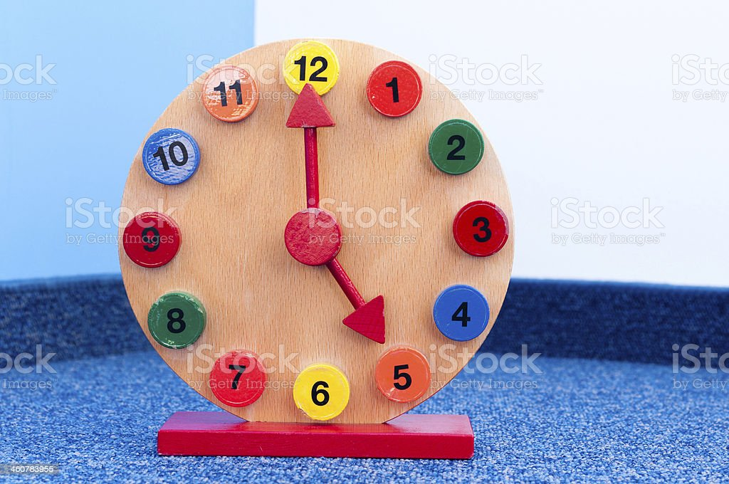 Wooden Learning Clock with pointer position at five stock photo