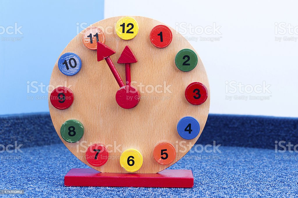 Wooden Learning Clock with pointer position at five to twelve stock photo