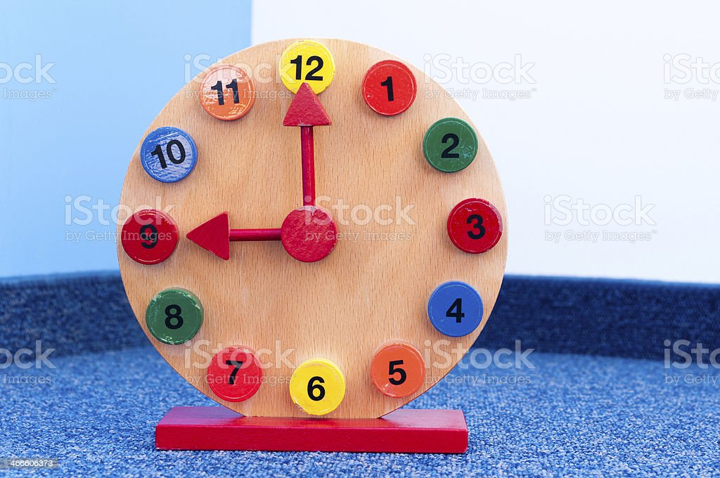 Wooden Learning Clock with pointer position at nine stock photo