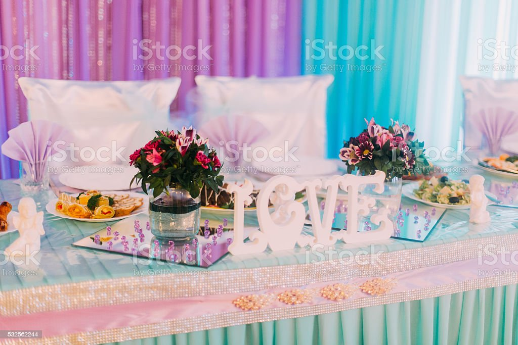LOVE wooden letters on a holiday decorated table with candles stock photo