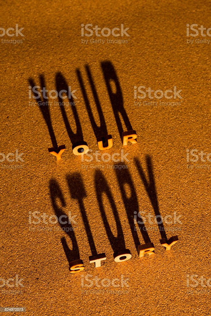 Wooden letters YOUR STORY and shadow on cork board stock photo