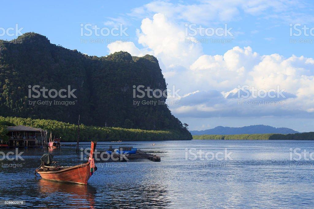 Деревянные длинными хвост лодке на голубой морской водой и солнечный свет отражать Стоковые фото Стоковая фотография
