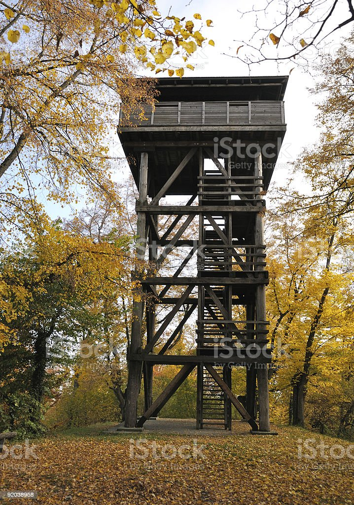 Wooden lookout tower between colorful trees in autumn stock photo