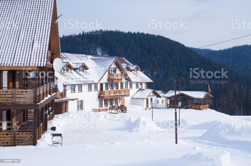 Wooden low-rise houses stand atop a hill in winter stock photo