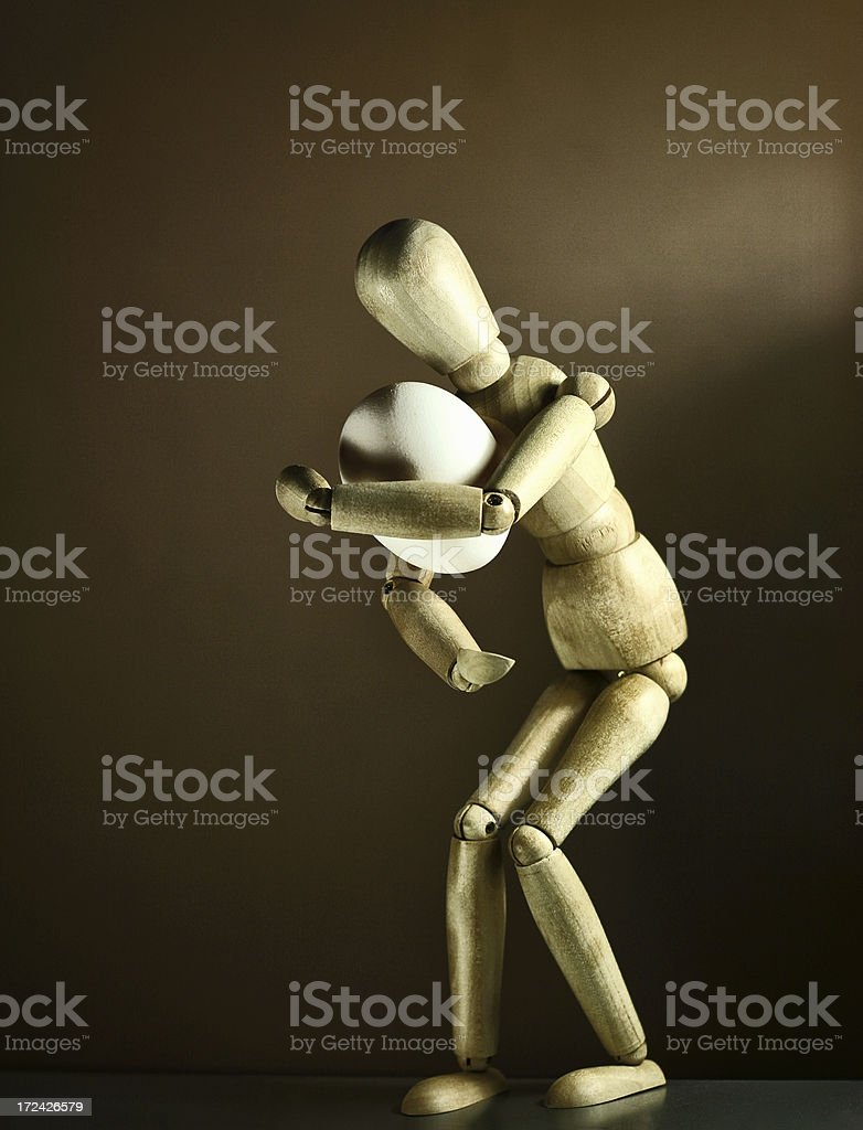 Wooden mannequin carrying egg stock photo