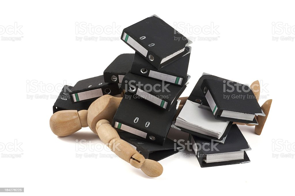 wooden mannequin clobbered by folders stock photo