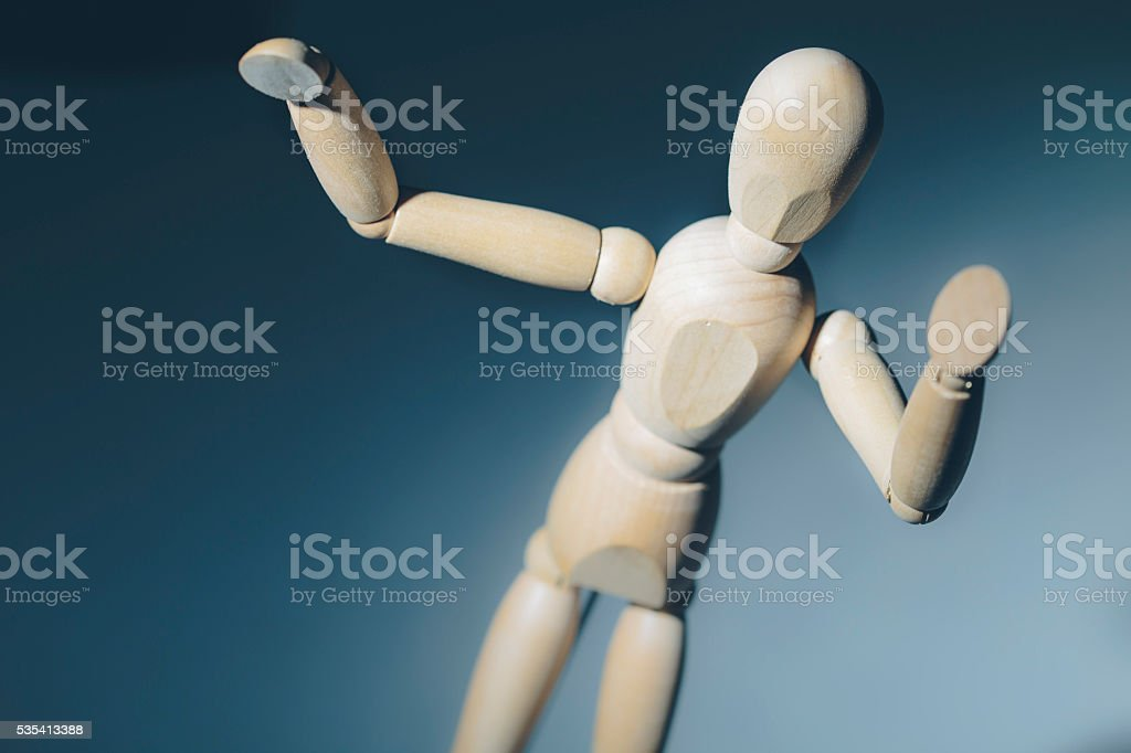 Wooden mannequin dummy on a blue background stock photo