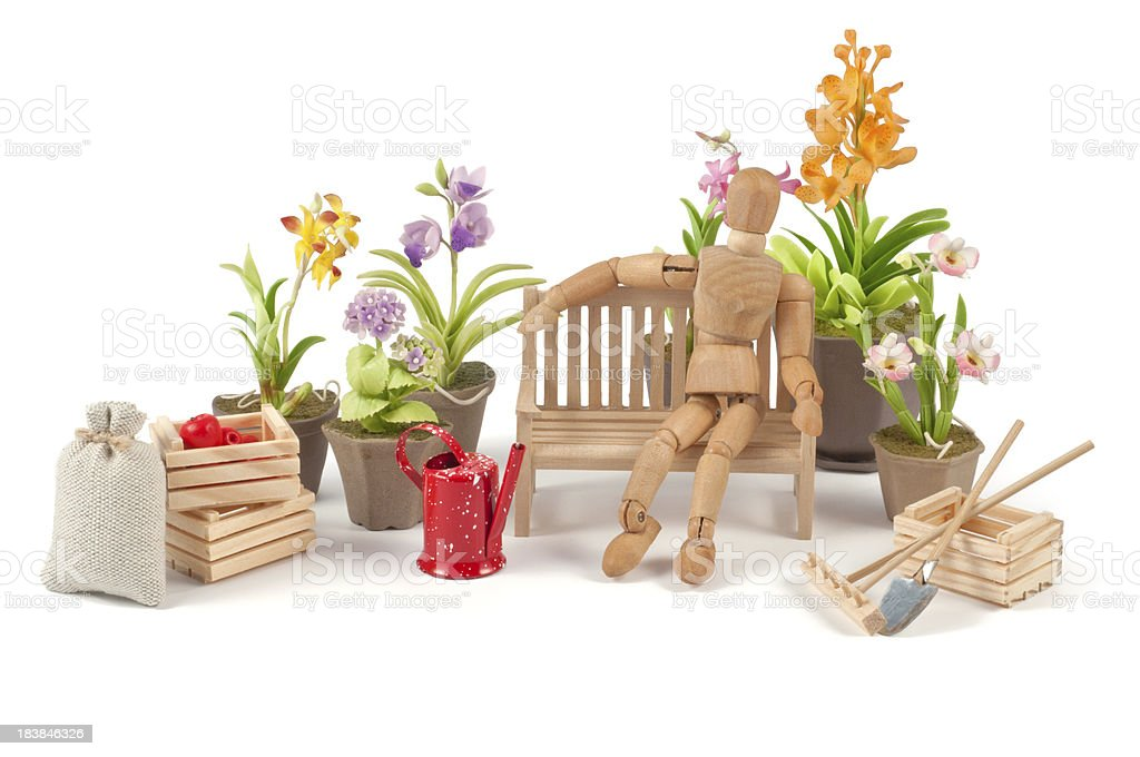 wooden mannequin enjoys his garden royalty-free stock photo