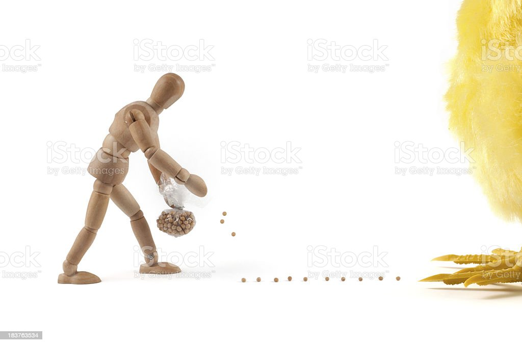 wooden mannequin feeding a chick monster stock photo