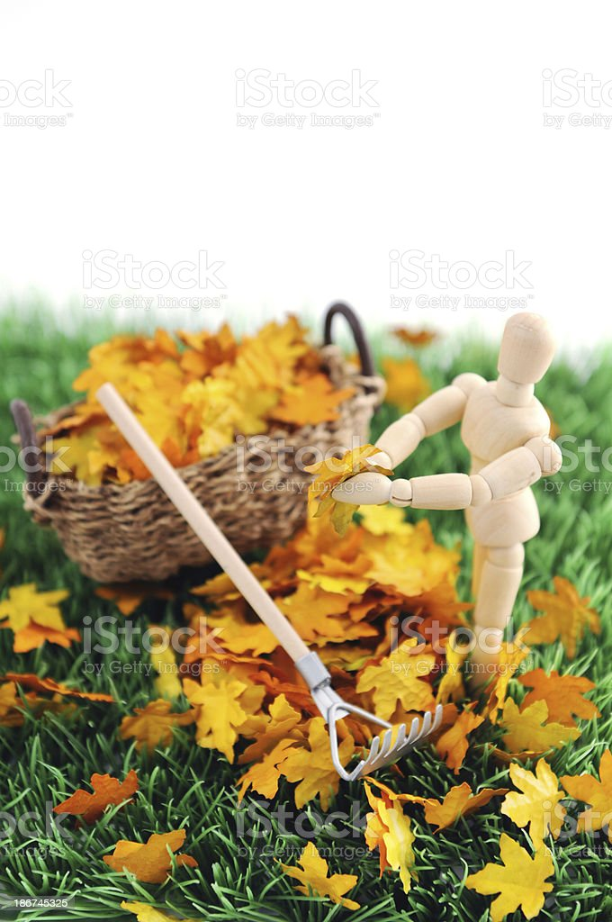 Wooden mannequin gardening with fork and leaf royalty-free stock photo