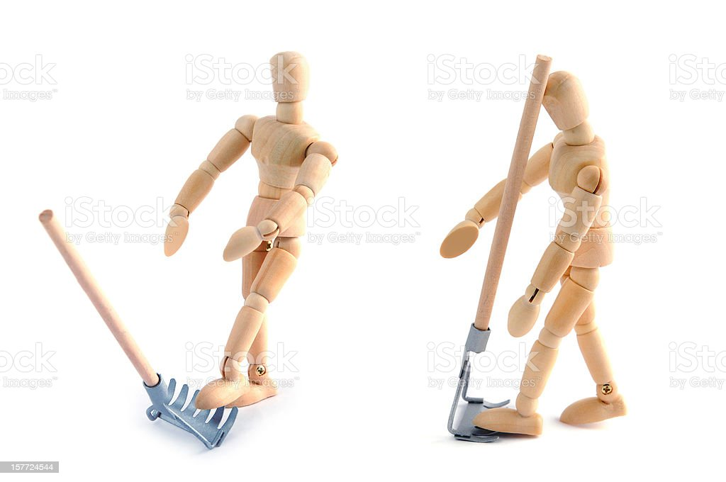 Wooden mannequin having accident of work with garden fork royalty-free stock photo