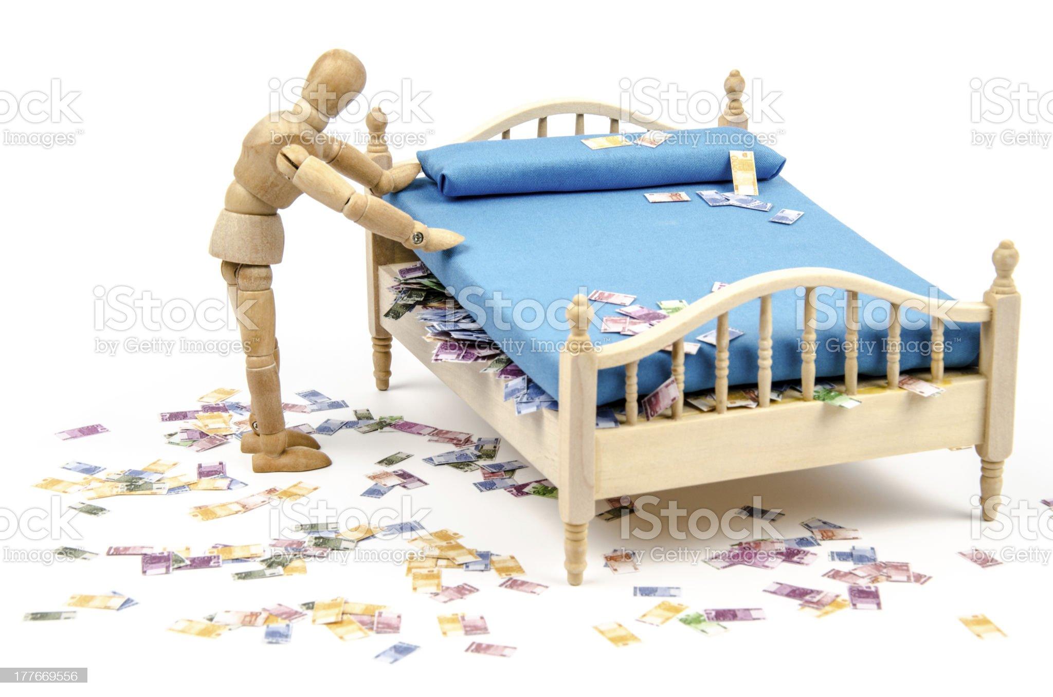 Wooden mannequin hides Euro money under the mattress royalty-free stock photo