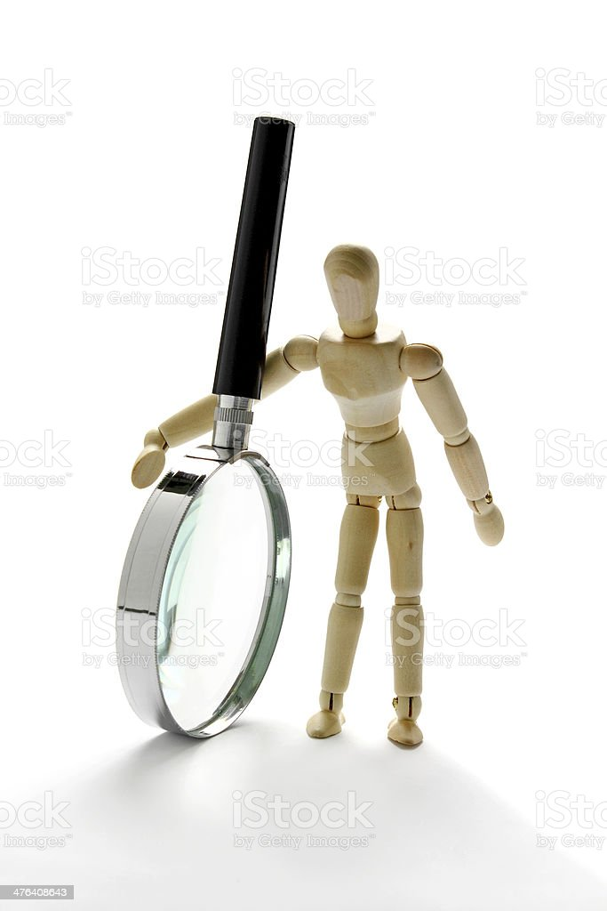 Wooden mannequin holding magnifying glass stock photo