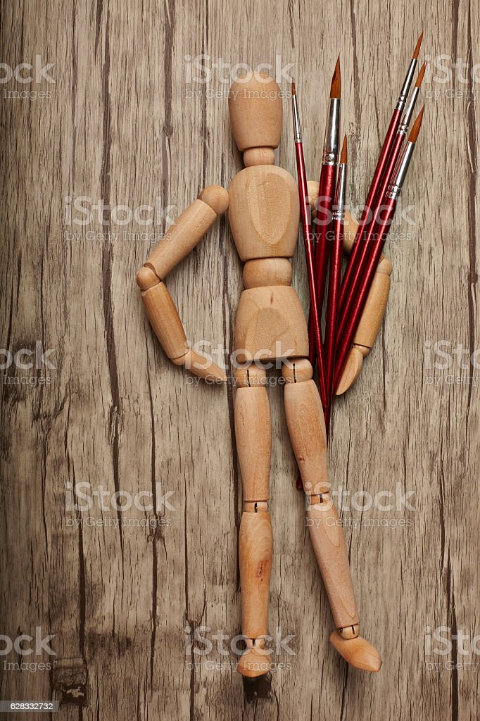Wooden mannequin holding paintbrush with wooden background stock photo
