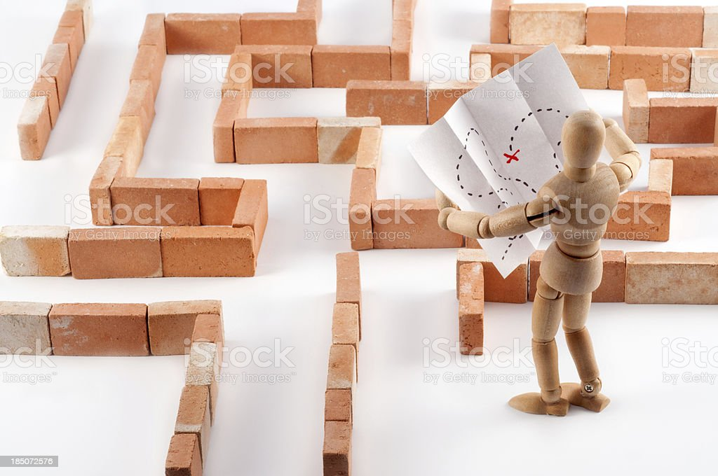 Wooden Mannequin in labyrinth with map royalty-free stock photo