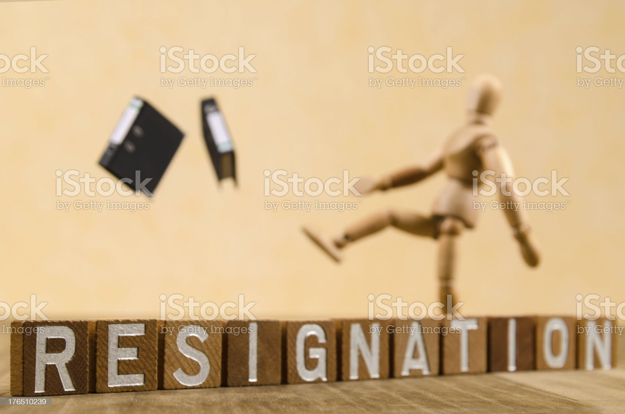 Wooden mannequin kicking folders because of resignation royalty-free stock photo