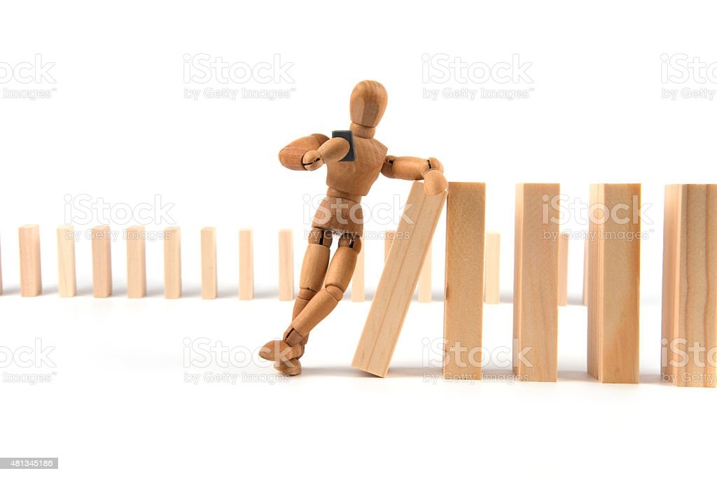 wooden mannequin leans careless on domino cascade with smartphone stock photo