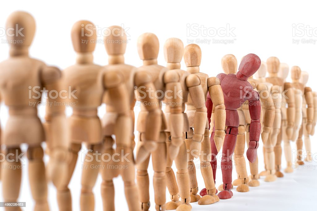 wooden mannequin looking out of the row stock photo